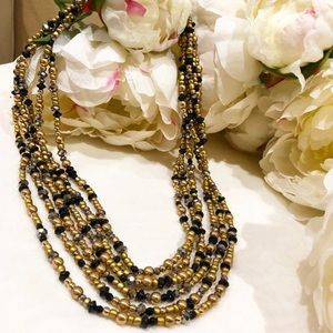 Layered gold and black necklace.